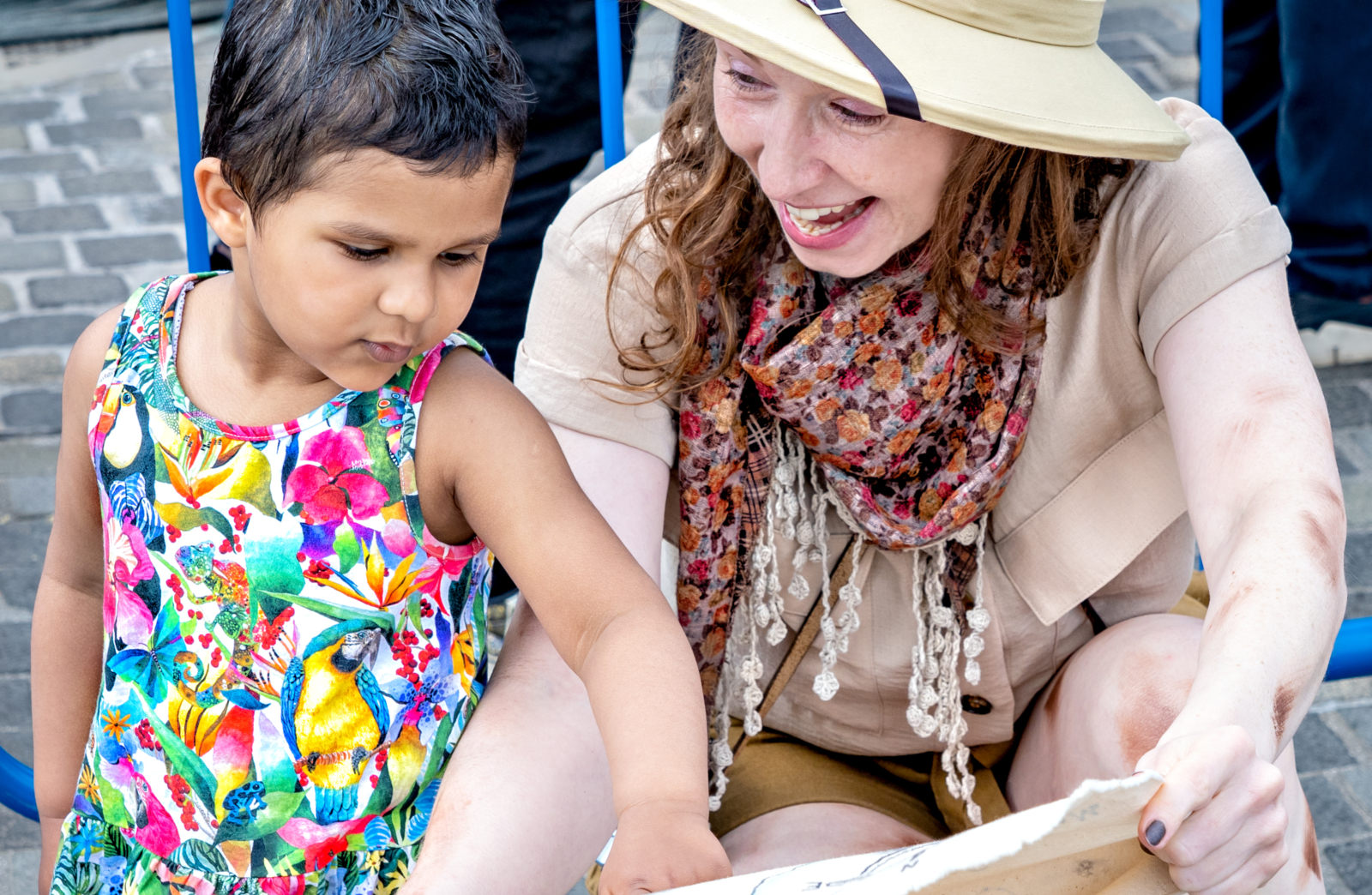 A woman dressed as an explorer shows a map to a young child